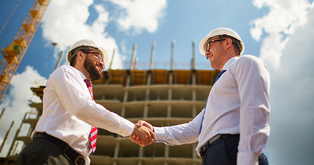 Two men shaking hands at construction site