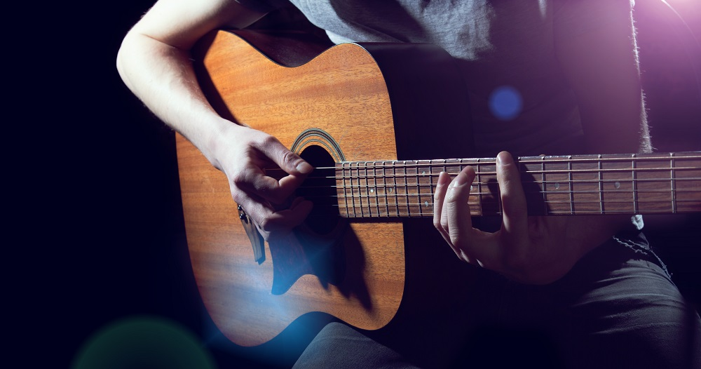 Musician playing on acoustic guitar on dark background